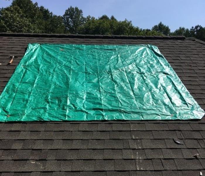 Portion of the roof with a blue tarp covering a hole