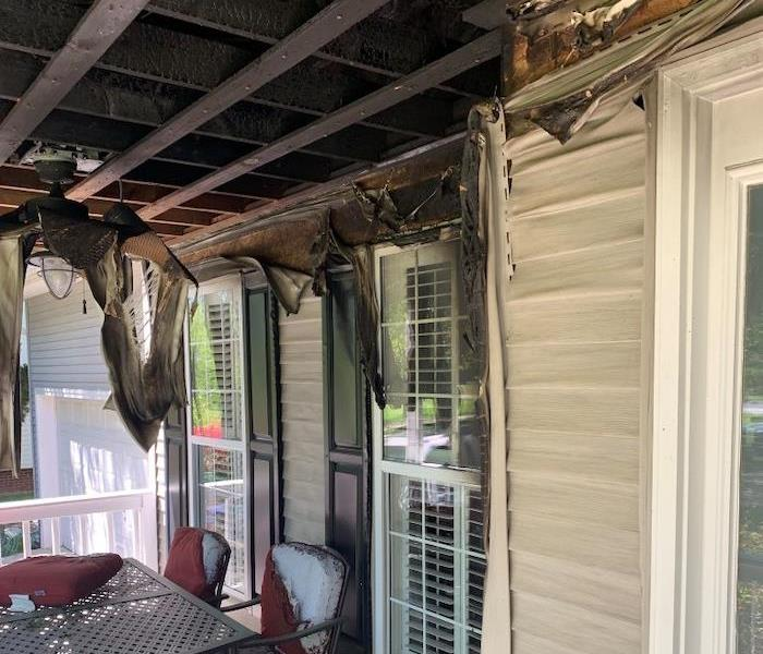 Fire damaged porch with hanging ceiling panels and damaged siding