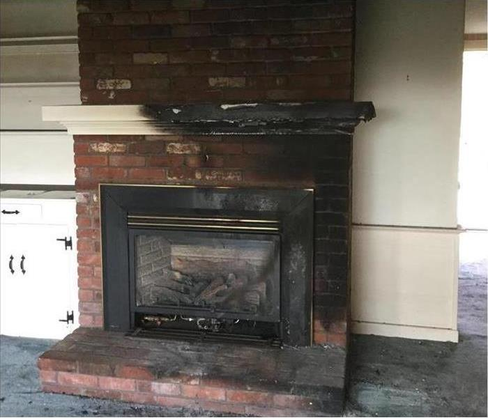 charred white wooden mantle above a sooty stained brick fireplace
