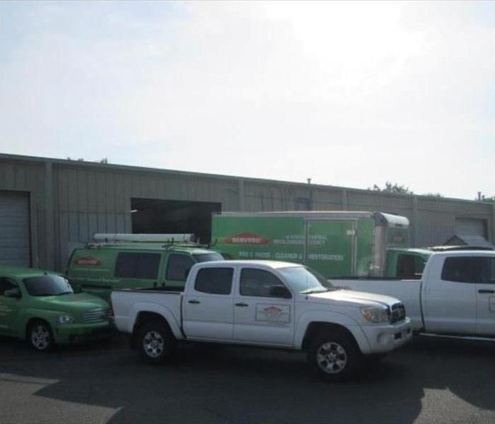 white and green SERVPRO trucks in a parking lot