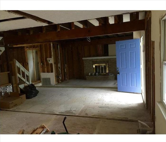 Home with blue door opened and subfloor showing