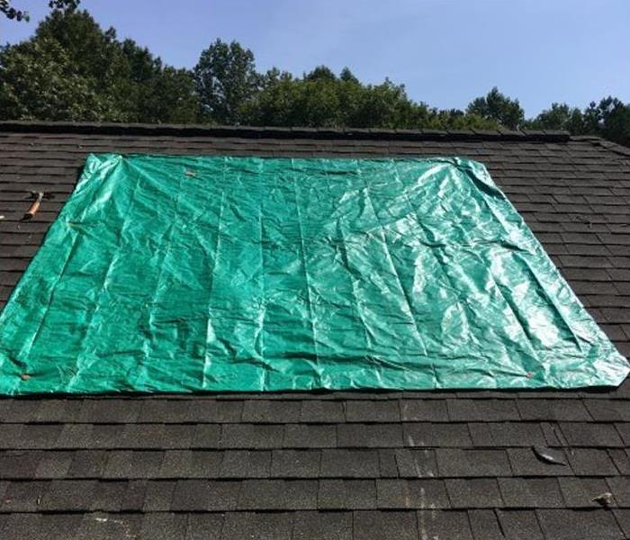 green tarp covering damaged shingled roof