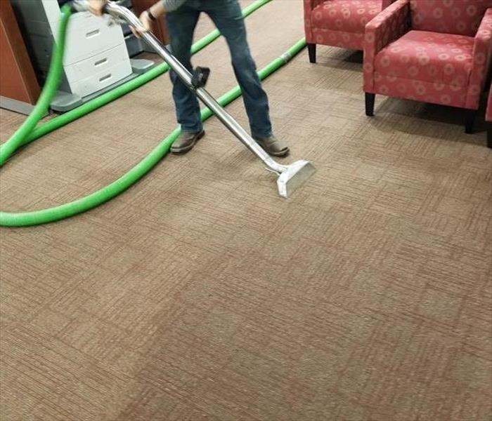 Technician cleaning office carpet with SERVPRO equipment
